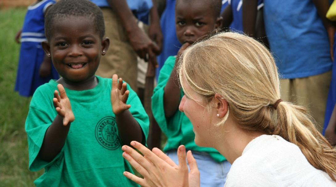 Una niña e interna de Trabajo Social aplaudiendo.